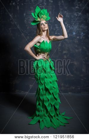 Beautiful sexy young girl woman lady model posing with hand in long paper green dress hair eccessories in fashion photo studio grey background