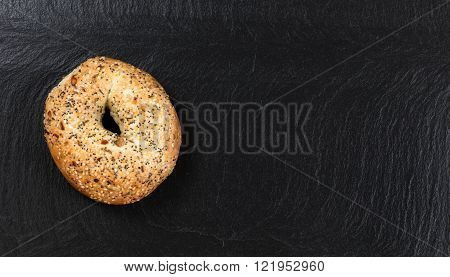 Overhead view of freshly baked seeded bagel on natural slate stone.