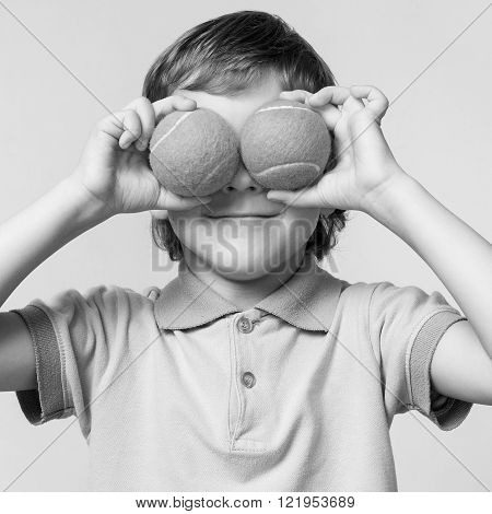 Children. Little boy holding tennis balls instead of the eyes, smiling, black and white