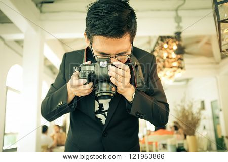 Photographer asian man take coffee photo in cafe