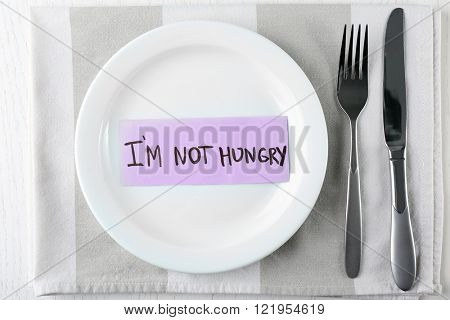 Piece of paper with text I'M NOT HUNGRY in plate on napkin with knife and fork, top view