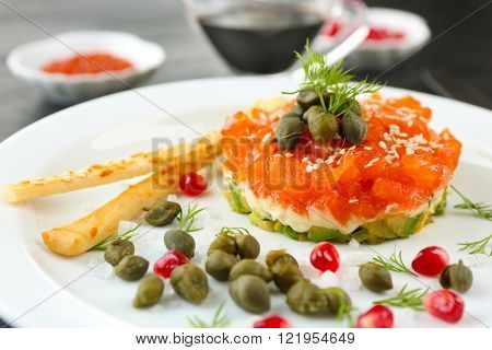 Fresh tartar with salmon, avocado and capers on white plate, close up