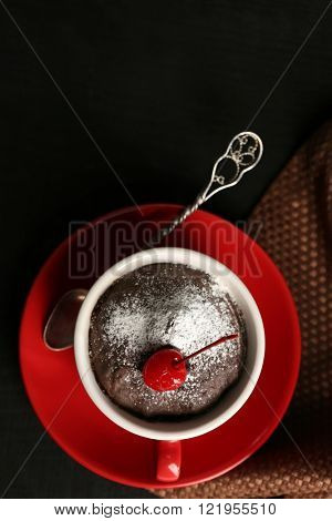 Chocolate cake in a red mug with a cherry on a wooden background, top view