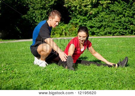 Woman does outdoor stretching with her personal trainer on a great summer day