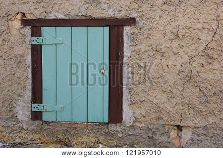 small window with a blue, closed shutter