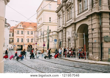 People cross the tram tracks on the street Malostranske namesti