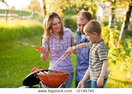 Family having a barbecue party, mother father and son standing around the grill