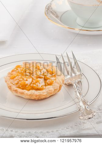 High key image of single bake apple tart with on white and silver plate.