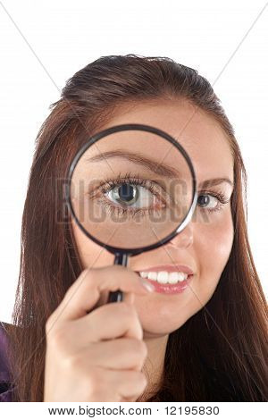 Smiling girl looking through magnifying glass