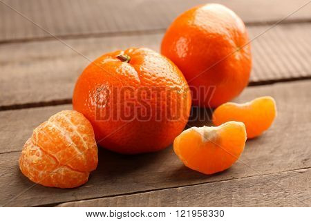 Unpeeled tangerines  with slices on the wooden table, close up