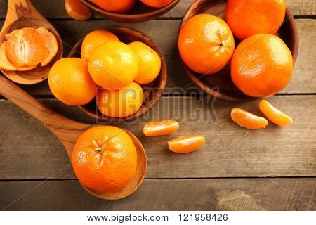 Peeled and unpeeled tangerines in wooden spoons and bowls, top view