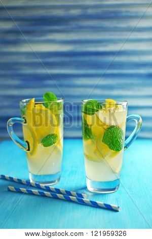Lemonade with lemon and mint on blue table against blue jalousie