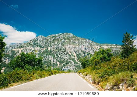 Beautiful asphalt mountain road under sunny blue sky