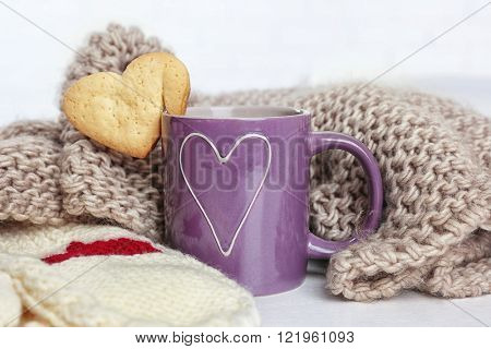 Heart shape cookie on cup of coffee with knitted cloth closeup