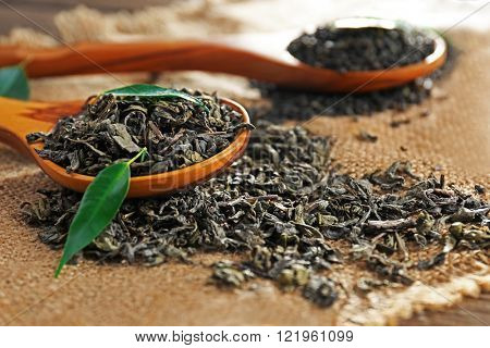 Granulated tea with green leaves on sackcloth closeup