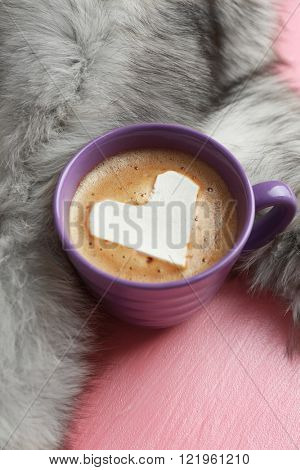 Cup of hot cappuccino with heart marshmallow and fur on pink background, close up