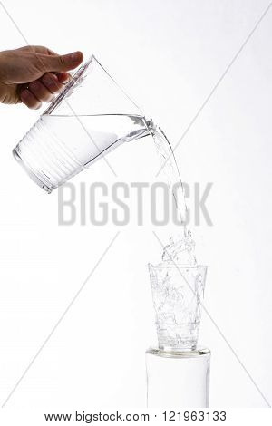 Water, vigorously poured from a jug overflowing splashing from a glass, on a white background