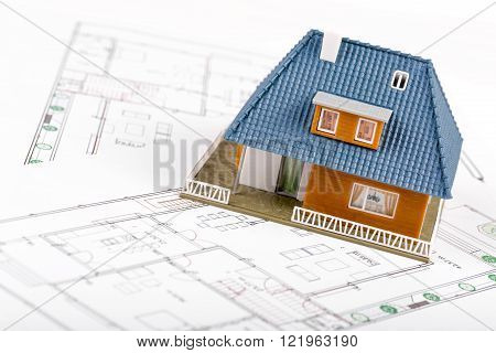 real estate development - house scale model on blueprints