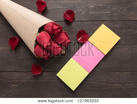 The arrangement of red roses flower with sticky notes are on the wooden background.