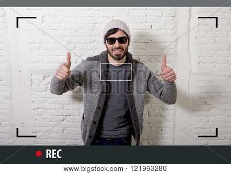 young attractive vlog hipster and trendy style looking man smiling happy talking to camera posing cool with attitude dressing informal in selfie and internet video blogger recording