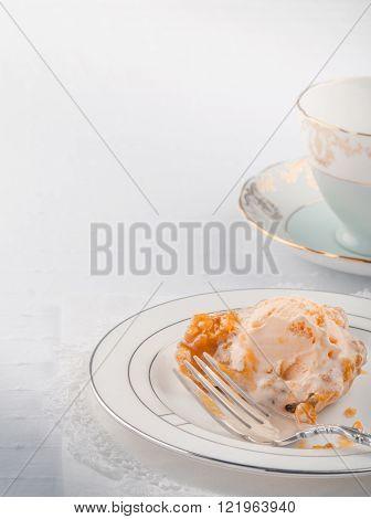 High key image of single bake apple tart with orange pineapple ice-cream.