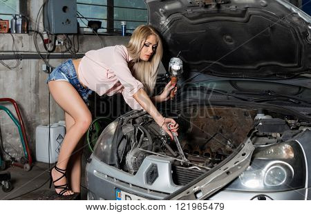 Full length of beautiful young woman repairing a car in a auto service.