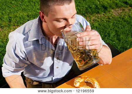 Man in traditional Bavarian costume - Lederhosen - drinking beer and eating pretzel