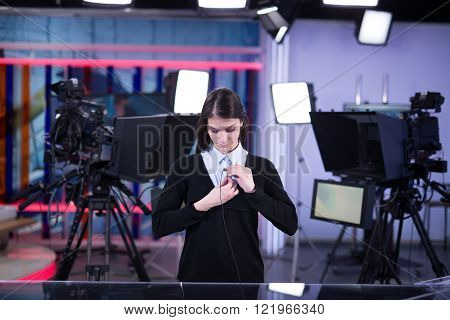 Television presenter recording in news studio.Female journalist anchor presenting report live in front of the audience.News camera,light equipment behind the scenes.Wireless microphone