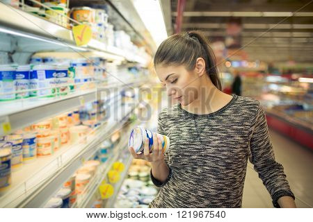 Young woman reading ingredients,declaration or expiration date on a diary product before buying it.Curious woman reading nutritional values of the food.Shopping in the supermarket grocery store.
