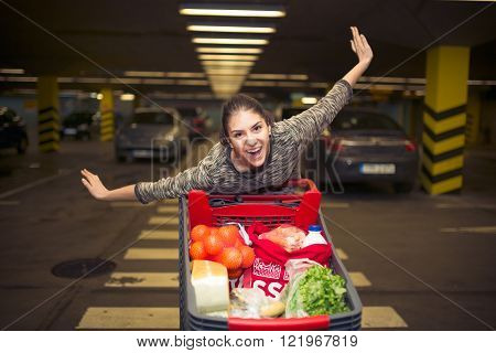 Attractive young woman smiling and pushing a shopping cart at supermarket parking lot.Concept of sale,discount,low prices.Happy customer satisfied with offer.Trolley full with variety of products