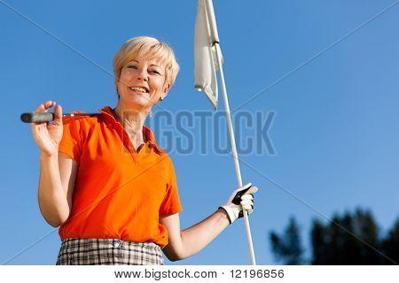 Mulher sênior, jogar golfe, segurando a bandeira na mão