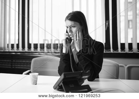 Worried stressed depressed office worker business woman receiving bad news emergency phone call at work.Looking confused and disappointed.Dismissed manager woman sitting in office.Getting fired.Argue