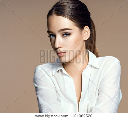 Charming young fashion model / photo-composition of brunette girl on beige background