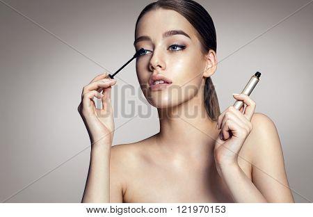 Woman applying black mascara on eyelashes with makeup brush / photos of appealing brunette girl on grey background