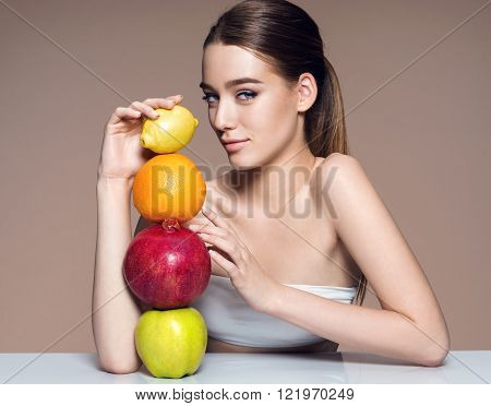 Beautiful and Healthy skin natural organic raw fresh food concept / portrait of girl with fruits mix on the table over beige backdrop