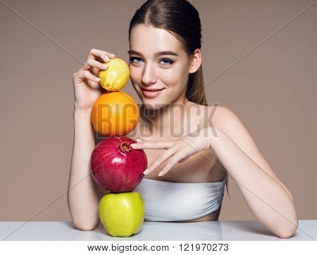Lovely girl with fruits mix natural organic raw fresh food concept / portrait of girl with fruits mix on the table over beige backdrop