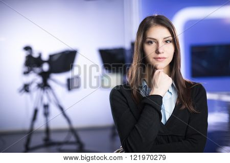 Television presenter recording in news studio.Female journalist anchor presenting business report,recording in television studio.News camera,light equipment behind the scenes. TV program editor.