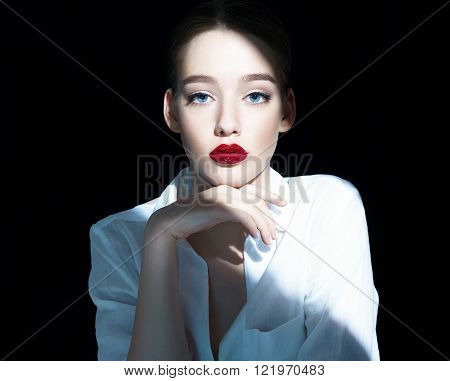 Portrait of a beautiful sensual brunette girl with red lips / close-up of an attractive girl of the European appearance in a white shirt, photography on a dark background.