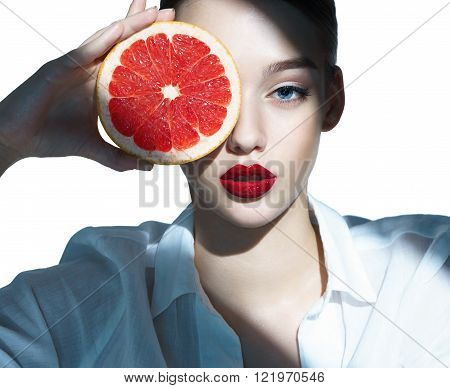 Lovely girl with pomelo slice, natural organic raw fresh food concept / close-up of an attractive girl of the European appearance in a white shirt - isolated on white background