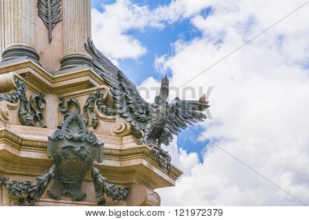 Low angle view of detail of independence monument with neo classical style column and ornate sculptures at the historic center of Quito in Ecuador.