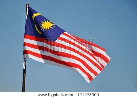 Waving Malaysia Flag on a flagpole with blue sky background ** Note: Soft Focus at 100%, best at smaller sizes