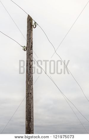 old wooden electric pole with wires in the background of the cloudy sky