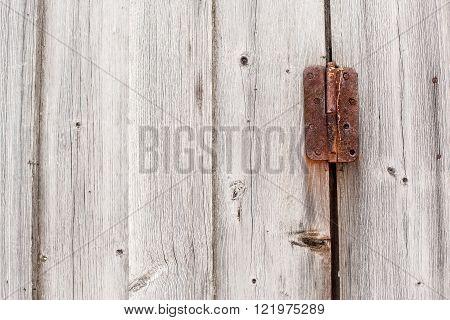 old rusty hinge on a wooden door