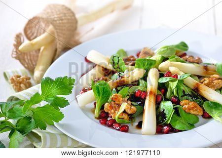 White asparagus on lamb's lettuce with candied walnuts, pomegranate seeds and balsamic vinegar