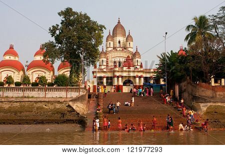 KOLKATA, INDIA - JAN 17: Hindu people bathing in the ghat near the Dakshineswar Kali Temple at the sunny day on January 17, 2013. The beautiful temple was built in Bengal architecture style in 1855