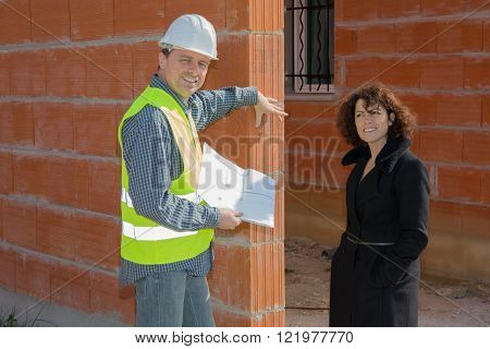 Professional architect and woman are having an explanation. They are standing near building and looking at each other with joy. The woman is holding documents. They are smiling