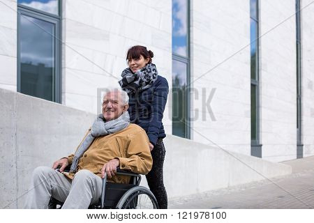 Picture of invalid male relaxing outdoor with daughter
