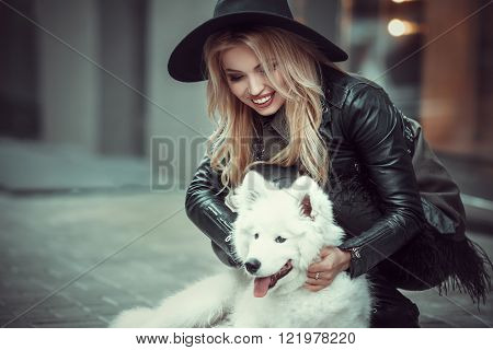 Beautiful stylishly dressed girl hugging on the street a large white dog. Woman hugging dog on a city street and experiences happiness