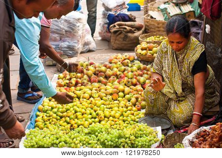 KOLKATA, INDIA - JAN 13: Asian woman sell fruits and vegetables on the crowd market street on January 13, 2012 in India. Only 0.81 perc. of the Kolkata's workforce employed in agriculture sector