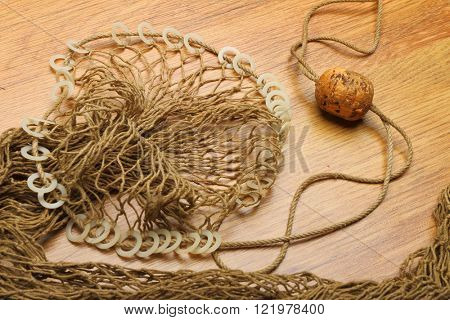 Fishing net with cork buoy on wooden plate. Industrial background.